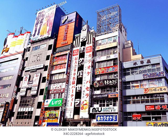 Buildings with store and restaurant signs on Yasukuni Dori, Shinjuku, Tokyo, Japan 2014