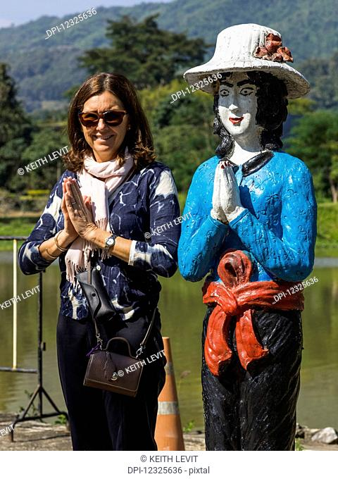 A female tourist poses in a similar pose to a Thai statue she is standing beside; Tambon Pa Tueng, Chang Wat Chiang Rai, Thailand