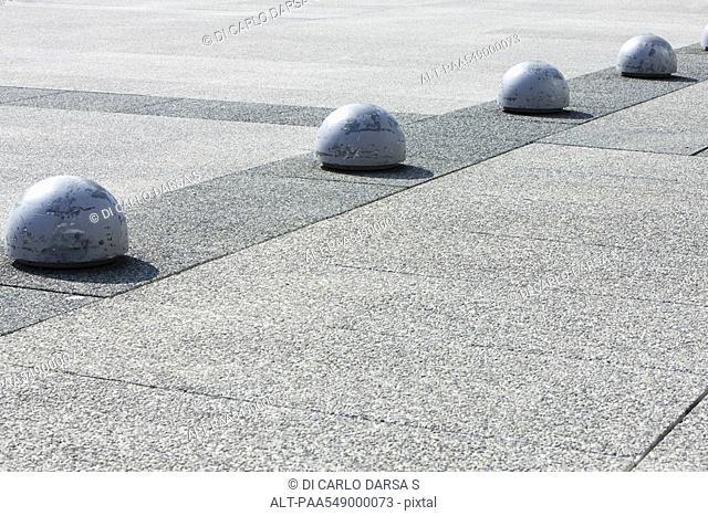Bollards in line along aggregate concrete pavement