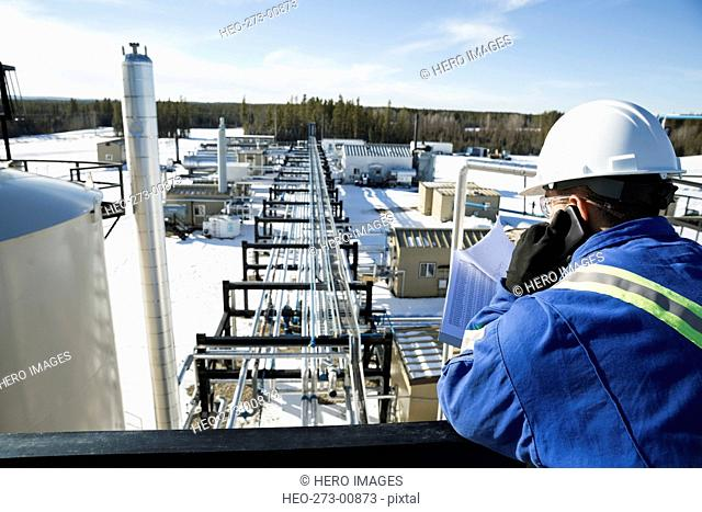 Engineer clipboard talking cell phone above gas plant
