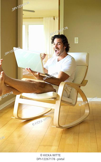 A man celebrating at what he reads on his laptop computer; Wailua, Kauai, Hawaii, United States of America