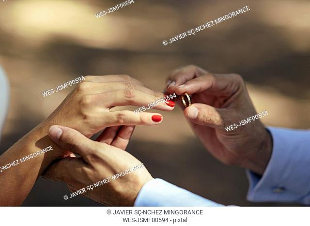 Groom putting wedding ring on finger of bride, close up