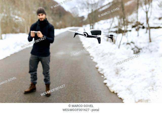 Spain, Asturias, man navigating a drone in the snowy mountains