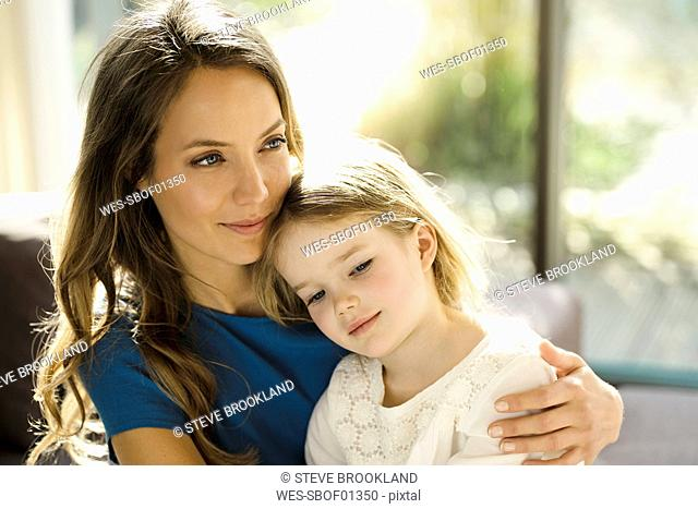 Portrait of smiling mother holding her daughter in front of window