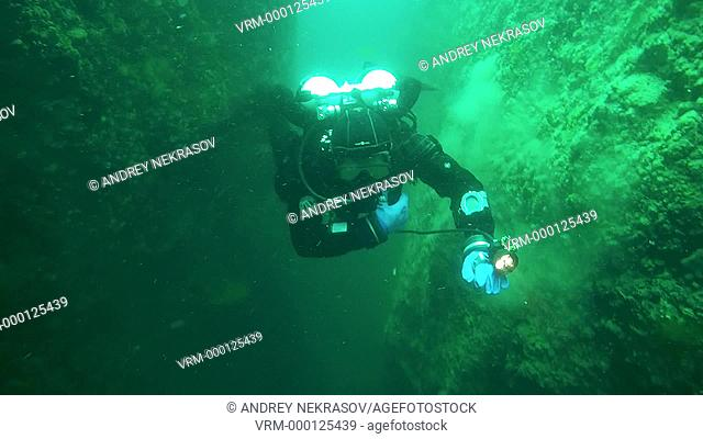 Technical diver dive into the depths swims through the underwater tunnel, lake Baikal, Siberia, Russia, Eurasia