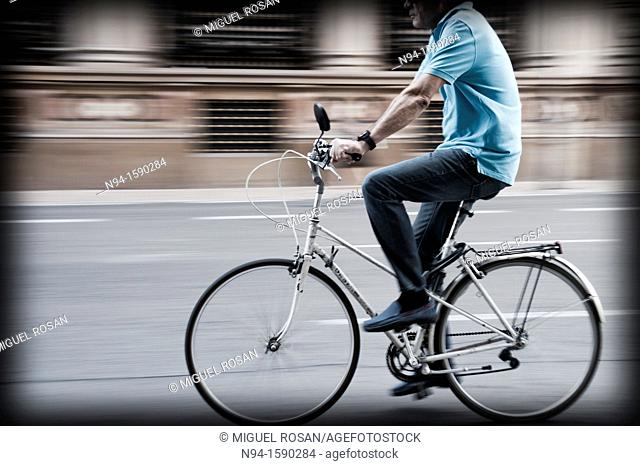 Young man biking through the city