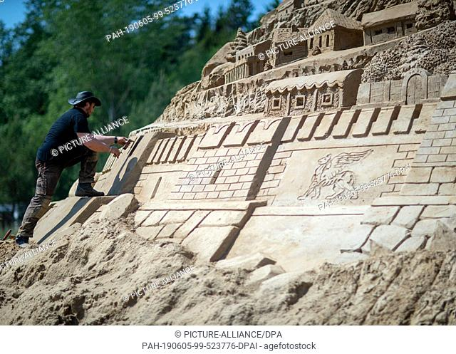 05 June 2019, Mecklenburg-Western Pomerania, Binz: Sand artists are working on a new record castle at the Sand Sculpture Festival. At 17
