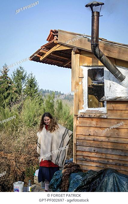 LORELEI IN FRONT OF HER CABIN, SHE LEFT EVERYTHING BEHIND TO COME BUILD AND LIVE IN HER WOOD CABIN IN THE CREUSE, FRANCE