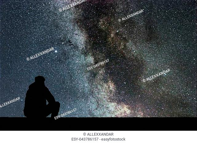 Milky Way. Night sky with stars and silhouette alone man looking at starry sky