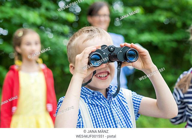 Germany, Boy with binoculars watching animals