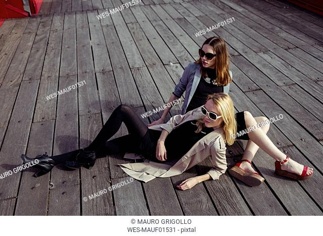 Two fashionable young women sitting on wooden floor wearing sunglasses