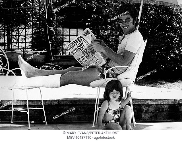 Alan Ball (1945-2007) rests his broken leg by the pool at his home. Having been made club captain of Arsenal in 1974, he broke his leg in April of that year
