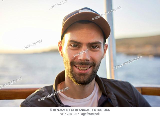 Portrait of happy smiling young French student man with cap during sunset in Malta, Europe