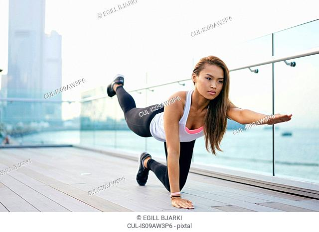 Young woman doing kneeling stretching exercise on waterfront, Hong Kong
