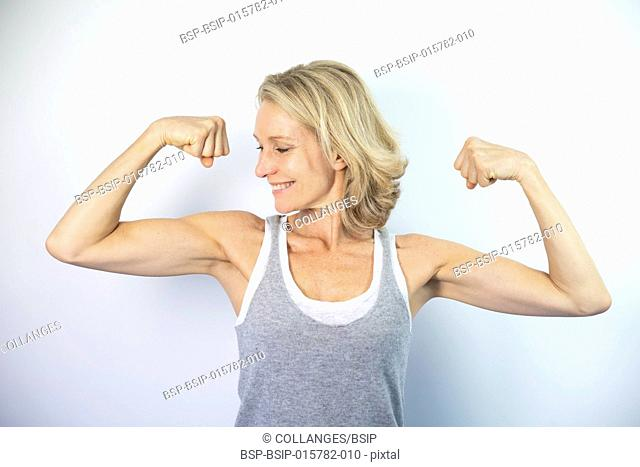 A woman looking at her muscles