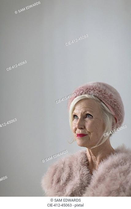 Portrait confident, elegant senior woman wearing pink fur