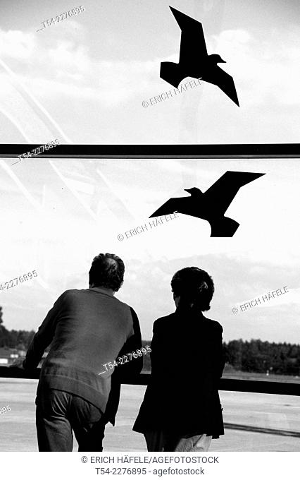 Two people watch to the Birds at Allgaeu Airport, Memmingen, Germany