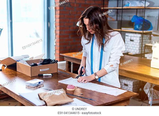 Young female fashion designer cutting fabric with scissors in studio