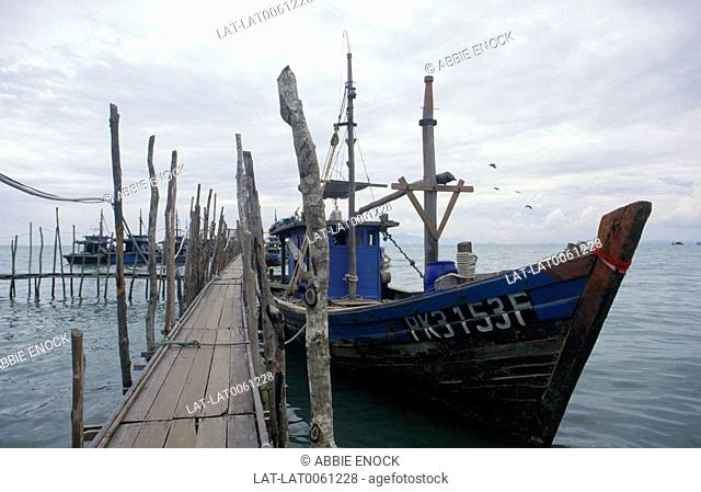 Telok Bahang island,and a local fishing boat moored to the bamboo jetty on stilts above the water