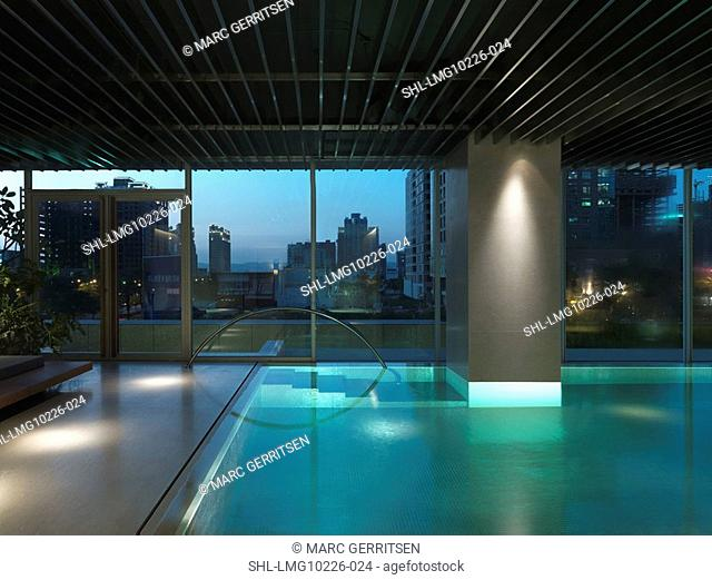 Indoor pool with view of downtown at dusk