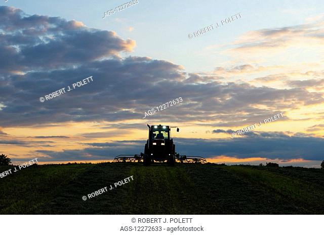 A farmer teds his alfalfa late in the day; Crawfordsville, Indiana, United States of America