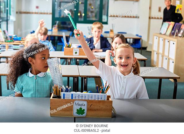 Schoolgirl with her hand raised in primary school classroom lesson