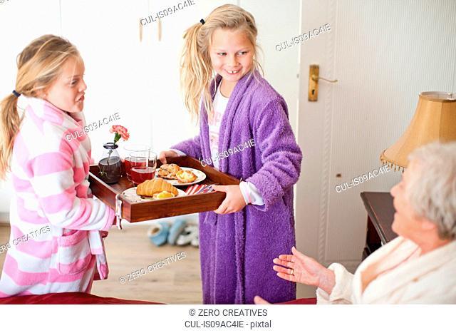 Granddaughters giving grandmother breakfast in bed