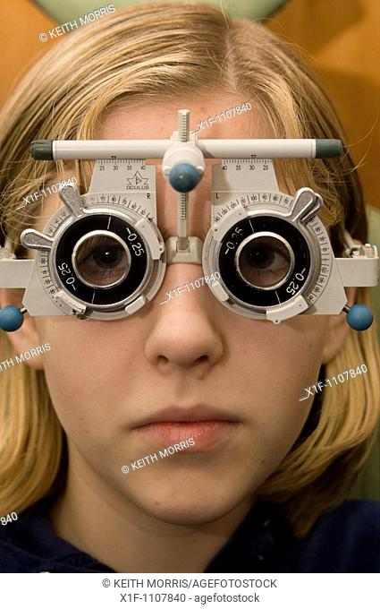 Teenage girl having her eyes tested by an optician