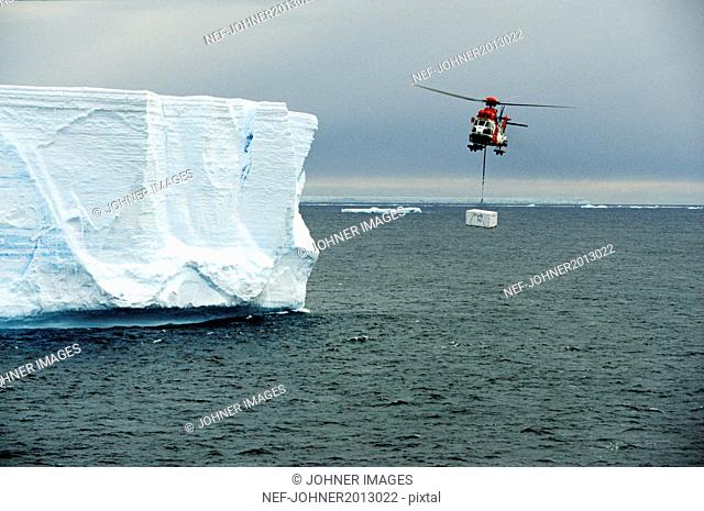 Helicopter carry freight over sea