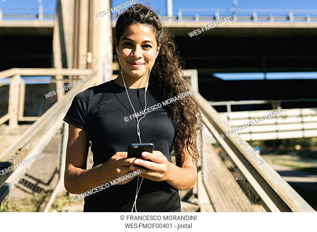 Portrait of sporty young woman having a break listening to music