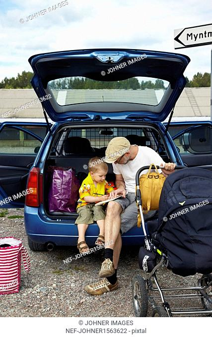 Father with son reading in car trunk