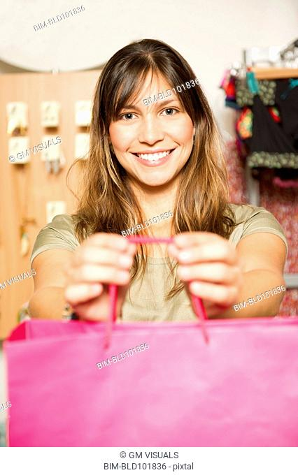 Hispanic woman holding out bag in store