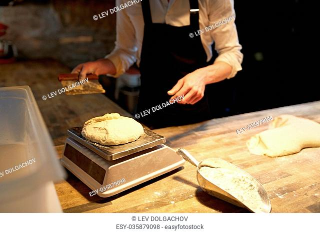 food cooking, baking and people concept - chef or baker with bench cutter portioning and weighing dough on scale at bakery