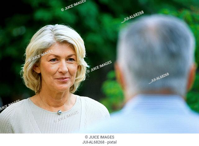 Head shot portrait of mature woman, with mature man in foreground