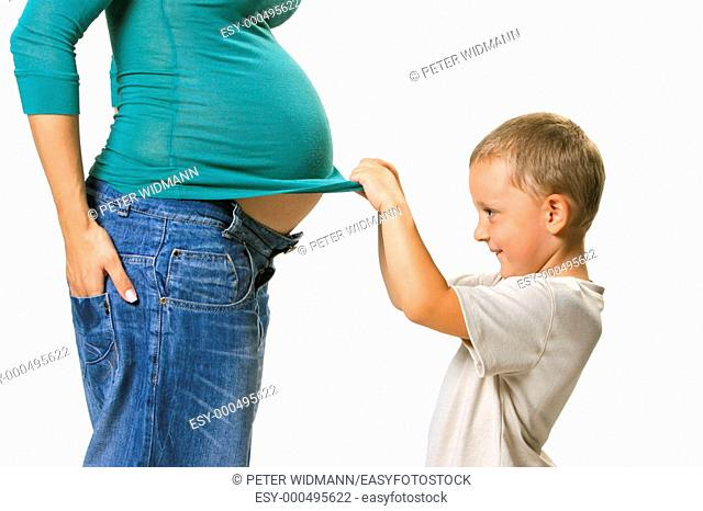 Son feels the belly of his pregnant mother