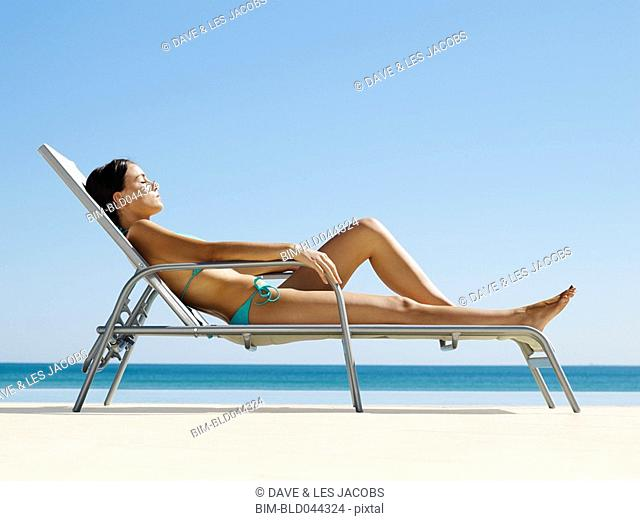 Hispanic woman sunbathing at beach