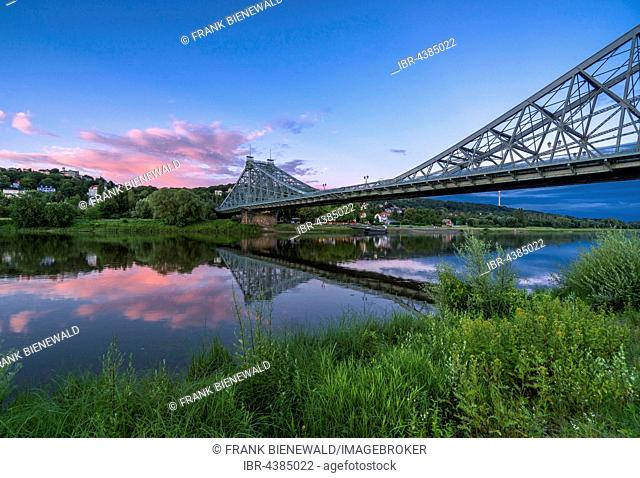 Historical bridge Blaues Wunder is crossing the river Elbe at dust with red cloud above it, Dresden, Saxony, Germany