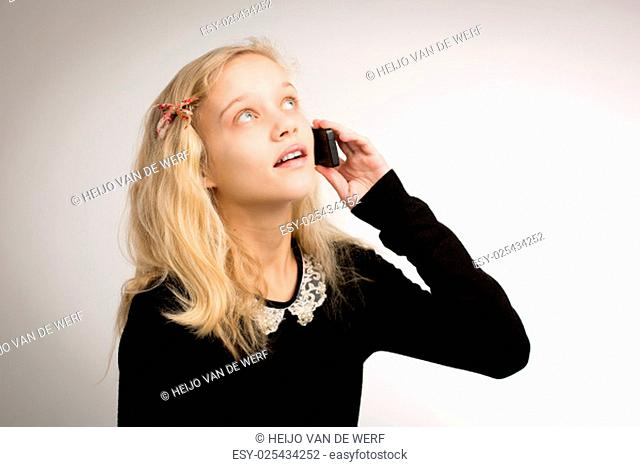 Studio portrait of a beautiful teenage blond girl talking on her cellphone looking up with blue eyes wearing a black top with a white collar isolated against a...