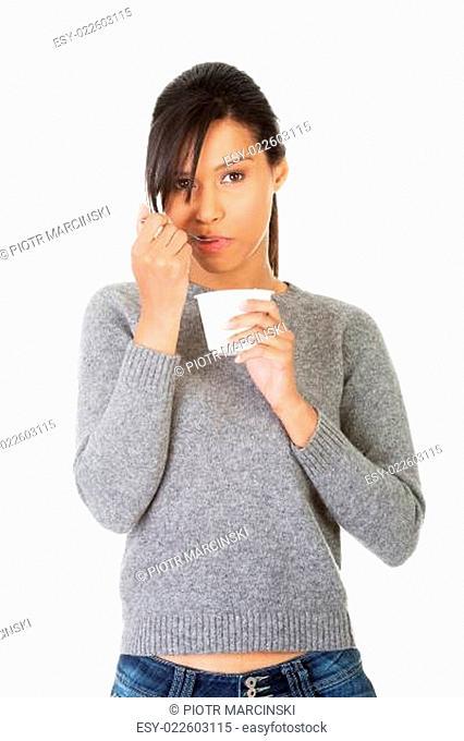 Young woman eating yogurt as healthy breakfast or snack