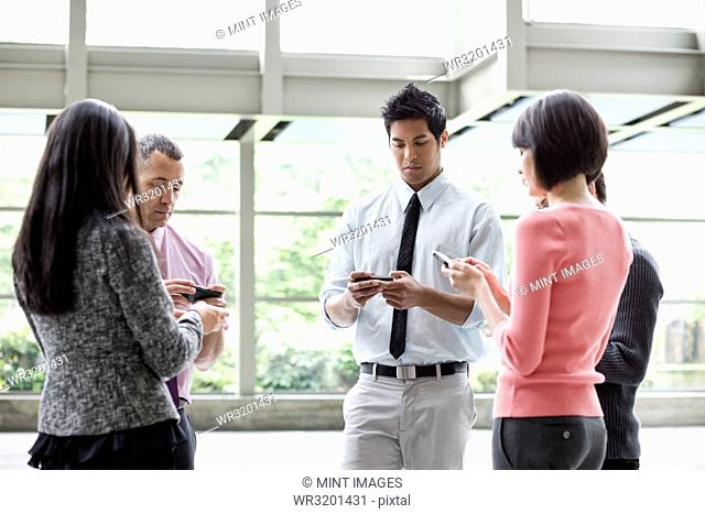 A mixed race group of male and female business people standing in the lobby area of a convention centre using their cell phones
