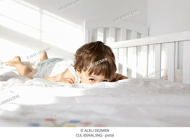 Candid portrait of female toddler peeking over bed quilt