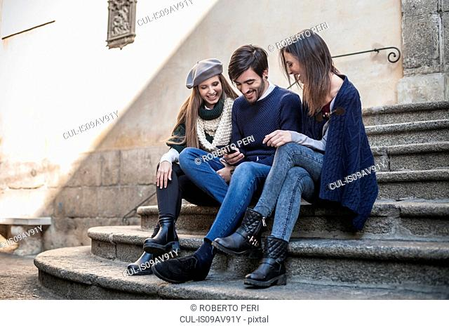 Friends sitting side by side on steps looking down at smartphone smiling