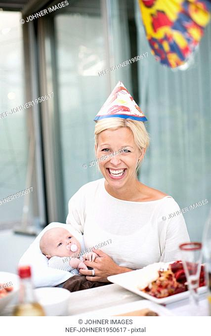 Smiling woman with baby at crayfish party, Stockholm, Sweden