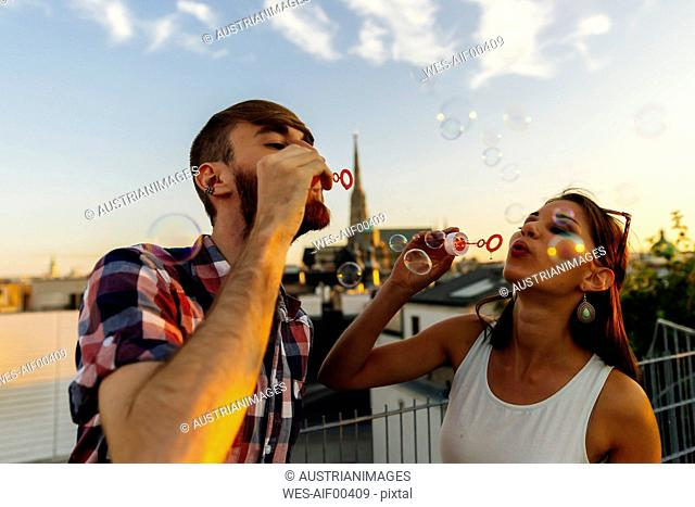 Austria, Vienna, young couple blowing soap bubbles on roof terrace