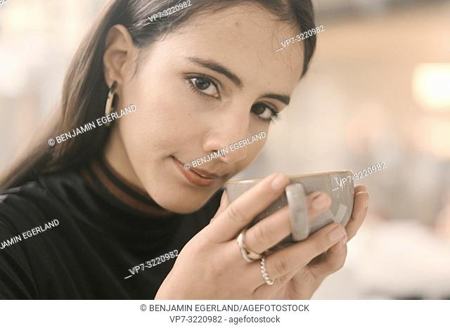 portrait of coy woman holding coffee cup, in Munich, Germany