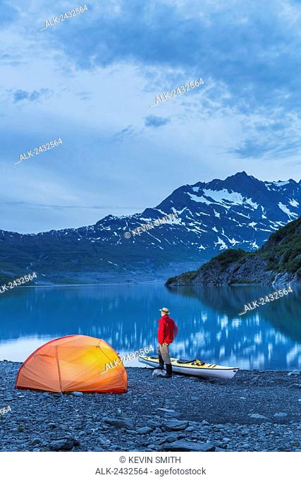 Man camping with a tent and kayak at Shoup Bay State Marine Park, Prince William sound, Valdez, Southcentral Alaska