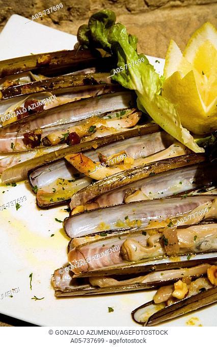 Razor shells with almonds and Iberian ham at La Galana cider house and restaurant, Gijon. Asturias, Spain