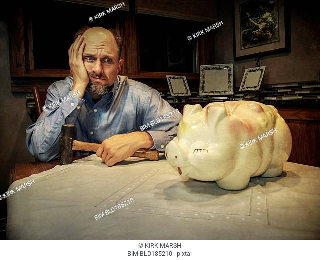 Caucasian man debating smashing piggy bank