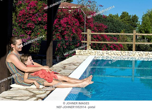 Woman with daughter relaxing at swimming pool, Sicily, Italy