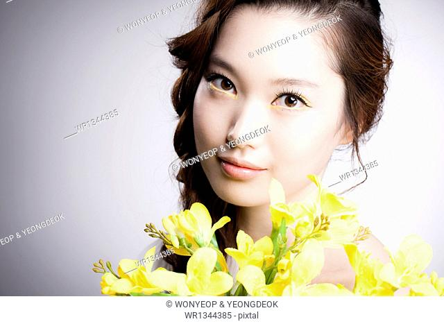 a woman with yellow flowers and yellow make up